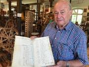 Gottlob Lutz zeigt ein altes Buchhaltungsbuch.