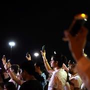 Mexikanische Bürger halten an der US-amerikanischen Grenze zum Gedenken an die Opfer von El Paso ihre leuchtenden Handys in die Luft. (Bild: Rey Jauregui/Keystone)