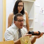 Firmenchef Hugo Klotz (gespielt von Bruno Lorandi) packt eine Flasche Wein aus, die er zum Geburtstag bekommen hat – beobachtet von seiner Frau Judith (gespielt von Daniela Jäckle). (Bild: Yvonne Aldrovandi-Schläpfer)