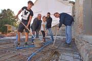 Fabian, Antonio, Rania, Andreas und Michael Mente verbuddeln die Zeitkapsel vor dem Betonieren im Boden. (Bild: Mario Testa)