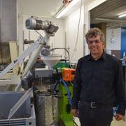 Christoph Gämperli, Präsident der St.Galler Saatzuchtgenossenschaft, mit einer der acht Pressen auf dem Areal in Flawil. Bild: Tobias Söldi