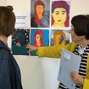 Silvia Peters von der Frauenfelder Bildschule schaut sich mit einer Besucherin die Porträts von Frauenfelder Schülerinnen und Schülern an. (Bild: Andreas Taverner)