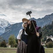 Eine Touristin mit Niqab macht auf der Höhenmatte in Interlaken vor der Jungfrau ein Selfie mit einer Frau in Tracht, aufgenommen am 4. Oktober 2017. (Bild: Keystone/Rolf Neeser)