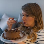 Depressed woman eats cake. Sad unhappy woman eating cake. Sad woman eating sweet cake. Close up of woman eating chocolate cake. food, junk-food, culinary, baking and holidays concept