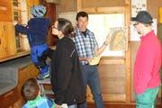Ernst Fuchs erklärt Familie Nikolic das Bienenhaus. (Bild: Manuela Olgiati)