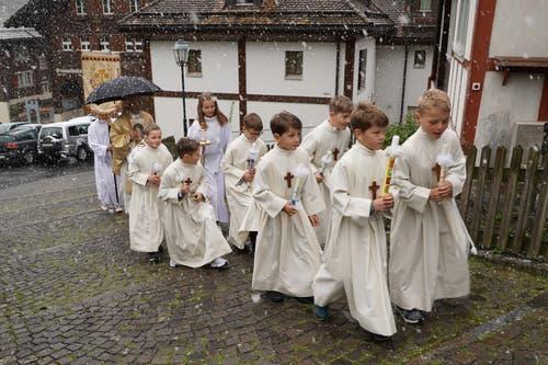 Bei leichtem Schneefall zogen die sieben Zweitklässler begleitet von Pfarrer Jan Strancich und den Ministranten in die Pfarrkirche Spiringen ein. (Bild: Franz Imholz, 28. April 2019)