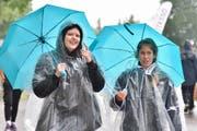 Agi und ihre Kollegin behelfen sich mit Regenschirm und Pelerine. (Bild: Mario Testa)