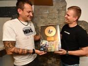 Reto Sturzenegger, Obergugger der Marktplatzpfuuser, bekommt von Präsident Samuel Svec eine Urkunde in Form einer goldenen Schallplatte, die ihn als Ehrenmitglied der Pfuuser auszeichnet. (Bild: Manuel Nagel)