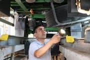 Mit einer Lampe kontrolliert Sandro Torre den Unterbau eines Lastwagens in der Prüfstelle Oberbüren. (Bild: Dinah Hauser)