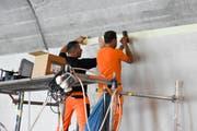 Bevor die Farbe aufgetragen werden kann, wird der Übergang zum Beton sauber abgeklebt. (Bild: Urs M. Hemm)