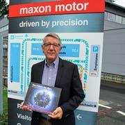 Autor Andreas Anderhalden präsentiert die neue Firmengeschichte vor dem Maxon-Hauptsitz in Sachseln. (Bild: Romano Cuonz (Sachseln, 2. November 2018))