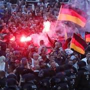 Demonstranten der rechten Szene zünden Pyrotechnik und schwenken Deutschlandfahnen. (Bild: KEYSTONE/DPA/Jan Woitas)