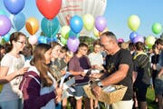 Vor der Abfahrt mit dem Heissluftballon nimmt Schulleiter Hansmartin Keller Glückwunsch-Karten der Schülerinnen und Schüler entgegen. (Bild: Mario Testa)