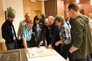 Bürger betrachten das Modell des Friedhofs Mogelsberg, der umgestaltet werden soll. (Bild: Urs M. Hemm)