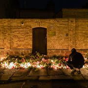 HALLE, GERMANY - OCTOBER 10: People mourn in front of the entrance to the Jewish synagogue on October 10, 2019 in Halle, Germany. Law enforcement authorities, after initially speaking of multiple attackers, are now referring to a single attacker who has been apprehended. A video, apparently streamed by the attacker live and with commentary from the shooting spree, shows him attempt and fail to force his way into the synagogue in Halle. He then, using what he describes as an improvised weapon, shoots a woman happening to pass by his car on the street and drives to a nearby kebab shop, where he shoots a man inside several times. Afterwards he fires at police blocking a street ahead of him, only to be wounded by returned fire. Towards the end of the video he states that he is bleeding and that he has been shot, and calls himself a ìcomplete loserî in an apparent apology to his perceived audience for not delivering the ìactionî he had anticipated. According to media reports the attacker has been identified as 27-year-old Stephan B. (Photo by Jens Schlueter/Getty Images) *** BESTPIX ***