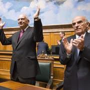 Der abtretende Bundesrat Pascal Couchepin bedankt sich 2009 für den Applaus des Parlaments. Rechts klatscht Bundespräsident Hans-Rudolf Merz. (Quelle: Keystone/Peter Schneider)