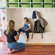Eine Betreuerin der Kita Small Foot in Luzern hilft einem Kind in der Garderobe beim Anziehen. (Bild: Dominik Wunderli, 22. Mai 2018)