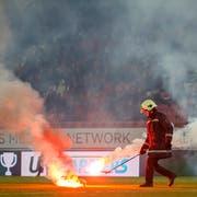 Das Löschen nützt nichts, der Schiedsrichter bricht das Spiel ab: Zuschauer aus dem GC-Sektor warfen Feuerwerkskörper auf den Rasen des Tourbillon (Bild: KEYSTONE)