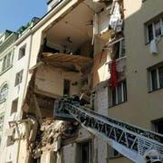 Nach einer Explosion in Wien klafft ein riesiges Loch in der Fassade eines Gebäudes. (Bild: Kevin Hofmann / EPA)