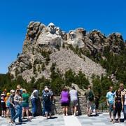 Posieren vor den Gründervätern: Die Porträts der US-Präsidenten George Washington, Thomas Jefferson, Theodor Roosevelt und Abraham Lincoln (v. l.) locken jedes Jahr über zwei Millionen Besucher in den Park. Der spektakuläre Weg führt direkt unter den Köpfen entlang. Bild: Alamy Stock Photo