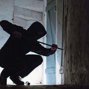 Im Bild (gestellte Szene) hebelt ein Einbrecher eine Türe auf. (Bild: Keystone / Silas Stein)