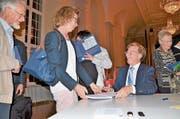Historiker Josef Kunz signiert nach dem Festakt im Festsaal des Klosters Muri sein Jubiläumsbuch. (Bild: Christian Breitschmid)