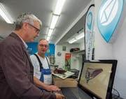Digitales und Laden vor Ort vernetzt: Der St.Galler Fachhändler Bruno Pfiffner (hinten) mit einem Kunden am Veloplace-Terminal. (Bild: Peter Hummel)