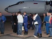 Wohlauf: US-Astronaut Nick Hague wird bei seiner Ankunft am Flughafen von Baikonur umarmt. In der Bildmitte sein russischer Kollege Alexej Owtschinin. (Bild: KEYSTONE/EPA ROSCOSMOS/ROSCOSMOS / HANDOUT)