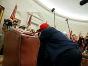 Trump für einmal ganz klein und kaum zu sehen: Der Rapper Kanye West sprang während eines Fototermins im Oval Office auf und umarmte den US-Präsidenten. (Bild: KEYSTONE/AP/EVAN VUCCI)