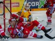 Der Puck in der Luft und die Spieler um Langnaus Torhüter Damiano Ciaccio am Boden (Bild: KEYSTONE/PATRICK B. KRAEMER)