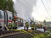 Der letzte Zugteil eines ICE ist am Freitagmorgen in Deutschland in Brand geraten. Aufgrund der Rauchentwicklung und der Löscharbeiten musste die vielbefahrene Autobahn 3 zwischen Dierdorf und Ransbach-Baumbach zunächst in beide Richtungen gesperrt werden. (Bild: KEYSTONE/EPA/SASCHA DITSCHER)