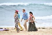 Prinz Harry (Mitte) und Meghan (rechts), die Herzogin von Sussex, unterwegs am Bondi Beach. (Bild: EPA/JOEL CARRETT)