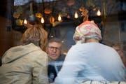 Zeno Schneider, Onkologe im Ruhestand, berät im Stadtluzerner Café Melissa's Kitchen zwei Krebspatientinnen. (Bild: Corinne Glanzmann, 1. Oktober 2018)