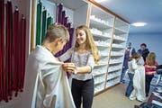 Elena Erni hilft bei der Anprobe – die neuen Gewänder braucht es, weil in Sursee so viele Kinder ministrieren wollen. (Bild: Pius Amrein (20.10.2018))