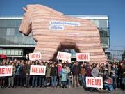 Personen demonstrieren in Bern mit einem Trojanischen Pferd gegen die Selbstbestimmungsinitiative der SVP. (Bild: KEYSTONE/PETER SCHNEIDER)