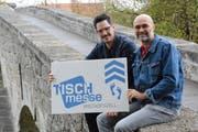 Die beiden Veranstalter, Lukas Zogg und Roland Geiger, präsentieren auf der alten Thurbrücke das Logo der Ausstellung. (Bild: Georg Stelzner)