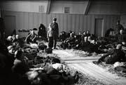 Robert Narev (Bildmitte) mit einem Soldaten nach der Ankunft im Hadwig-Schulhaus im Februar 1945. Die Turnhalle wurde damals als Strohlager für jüdische Flüchtlinge hergerichtet. (Bild: Ringier-Archiv)