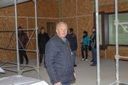 Erich Schaffer, Schulpräsident und Baukommissionspräsident, im neuen Mehrzweckraum. Im Hintergrund Interessierte. (Bild: Manuela Olgiati)