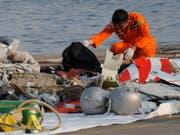 Indonesische Rettungskräfte untersuchen im Meer gefundene Wrackteile des Flugzeugs. (Bild: KEYSTONE/AP/TATAN SYUFLANA)