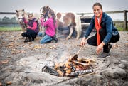 Denise Neuweiler beim Feuermachen an der Grillstelle oberhalb von Zuben mit den zwei Töchtern Flurina (links) und Leana.Bild: Reto Martin