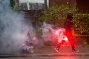 Ein Krawalltourist läuft mit der Pyro nach seiner Attacke gegen eine Frau weg. (Bild: Ennio Leanza/Keystone (Zürich, 1. Mai 2015))