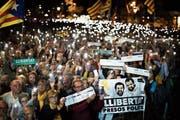 Separatisten-Anhänger demonstrieren für die Freilassung der inhaftierten Politiker, darunter Jordi Sànchez und Jordi Cuixart, die auf dem Poster abgebildet sind. (Bild: Emilio Morenatti/AP (Barcelona, 16. Oktober 2018))