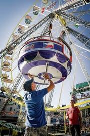 Das Herzstück des Herbstjahrmarktes: Arbeiter montieren die Kabinen des Riesenrads. (Bild: Ralph Ribi)