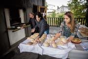 Backen am Samstagvormittag: Joe Müggler steht am Ofen, während die Co-Präsidentinnen Doris Roos Kliem und Alice Schlaginhaufen die verschiedenen Backwaren vorbereiten. (Bild: Reto Martin)