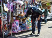 Auf der Suche nach einer neuen Dienstwaffe? Oder nach Handschellen? Ein Polizist begutachtet am Fischinger Jahrmarkt das Angebot eines Spielzeugstandes. (Bilder: Christoph Heer)