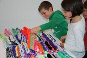 Die Kinder freuen sich über die Stirnbänder, welche sie im Dunkeln sichtbar machen werden. (Bild: Flurina Lüchinger)