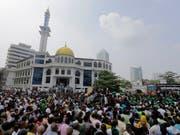 Anhänger des geschassten Ministerpräsidenten Ranil Wickremesinghe demonstrieren ihre Unterstützung vor dem offiziellen Sitz des Regierungssitz in Colombo. (Bild: KEYSTONE/AP/ERANGA JAYAWARDENA)
