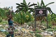 Eine nigerianische Frau an einem Schild, das vor verunreinigtem Land in der Gemeinde Ogale warnt. (Bild: Tife Owolabi/EPA (Nigerdelta, 9. März 2016))