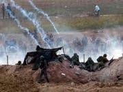 Israelische Soldaten und palästinensische Demonstranten treffen an der Grenze zum Gazastreifen aufeinander. (Bild: KEYSTONE/EPA/JIM HOLLANDER)