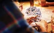 Ein Jass wird geklopft: Ein Spieler hält ein Blatt Riedweg-Karten in der Hand, die wohl die traditionellen Bilder zeigen, aber typografisch von Grund auf überarbeitet wurden. (Bild: Jens Riedweg)